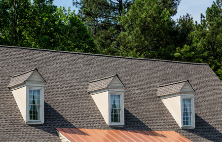 roof top: Three white wood dormers on an old grey shingle roof