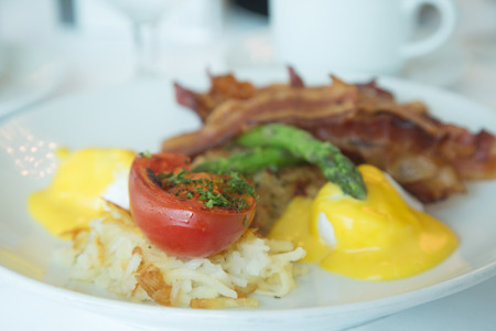 broiled: Eggs Benedict with hash browns, broiled tomato, asparagus and bacon Stock Photo