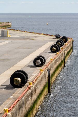 Tires chained to a concrete pier for boat bumpers