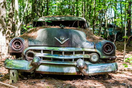 junk: DETROIT, MICHIGAN - May 11, 2015: Wreck of a vintage Cadillac. The logo has changed, but this original was based on coat of arms for Le Sieur Antoine De La Mothe Cadillac, the man who founded Detroit