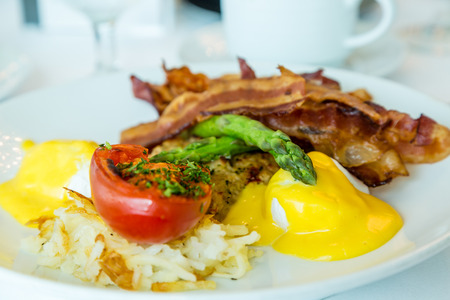 browns: Eggs Benedict with hash browns, broiled tomato, asparagus and bacon Stock Photo