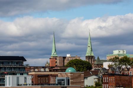 steeples: Two green church steeples above old brick buildings in Saint John, New Brunswick, Canada Stock Photo