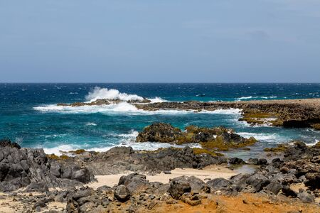 volcanic: Black volcanic rock on shore of Aruba Stock Photo