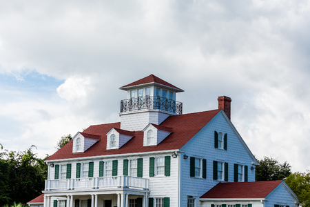 Cliassic white home with red roof, dormers and widows walk