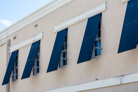 louvered: Blue storm shutters open on a new stucco building