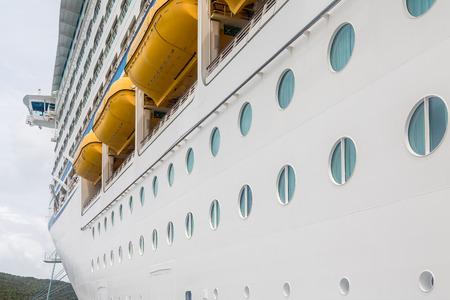lifeboats: Portholes beneath lifeboats on a massive white luxury Cruise ship