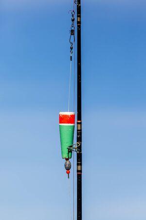Fishing pole: Colorful float on fishing pole on blue sky