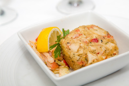 lemon wedge: An appetizer of crab cake with lemon wedge and parsley