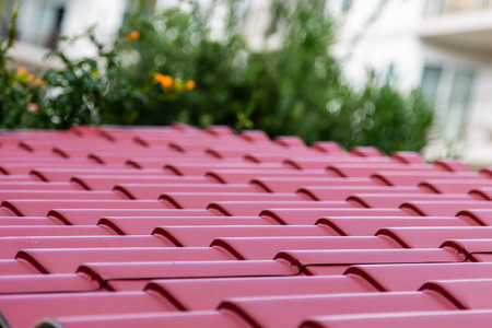 A corrugated red metal roof on a home