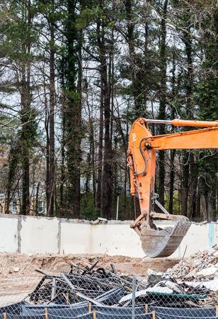 front end loader: Arm and bucket on an orange front end loader at a demoliton site