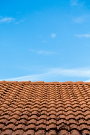 soot: Orange tile roof under blue sky with soot from chimney