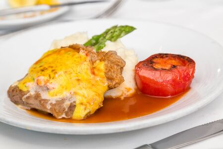 broiled: A breaded and baked pork cutlet with sauce and gravy, mashed potatoes, asparagus and broiled tomato
