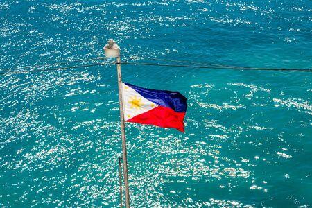 philippine: Philippines Flag on Pole Over aqua ocean