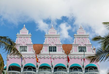 awnings: Colorful building in Aruba with pink stucco, flags and green awnings