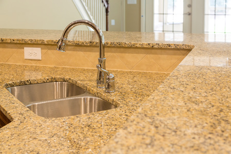 granite kitchen: New stainless steel sink in granite countertop in a new home Stock Photo
