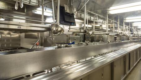cocinas industriales: Utensilios de acero inoxidable que cuelgan en una cocina comercial