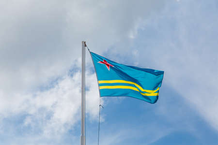 aruba flag: Yellow stripes and red star on field of blue. National flag of Aruba