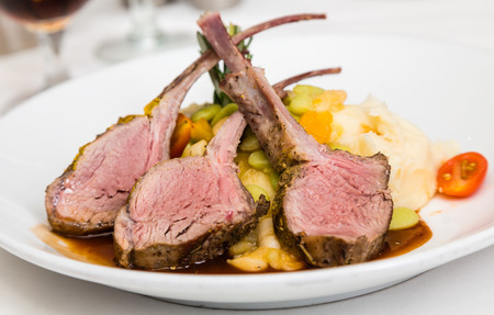 meat dish: Three medium rare lamb chops on a bed of vegetables