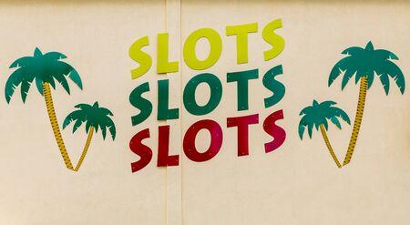 slot machines: Signos y palmeras en un casino con máquinas tragamonedas