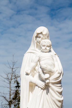 mary mother of jesus: A white stone statue of the Madonna and Jesus under nice sky