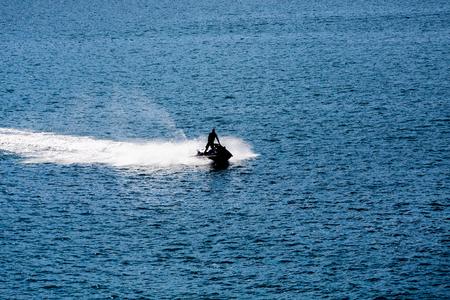 sillouette: Jet Ski Sillouette on Blue water of calm bay