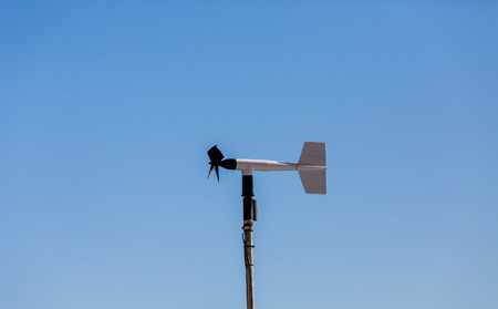 A black and white wind meter on a blue sky