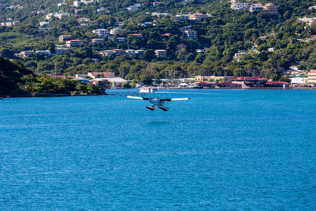 hydroplane: Small seaplane about to land on blue water in bay Stock Photo