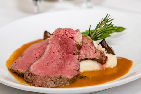 Serving of rare prime rib of beef with mashed potatoes and garnished with rosemary Imagens