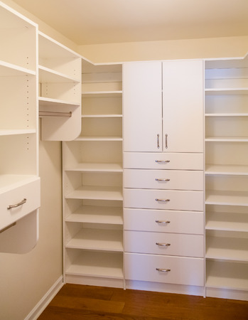 walk in closet: Custom white wood cabinetry in a walk in closet