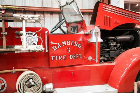 antique fire truck: An old red, antique fire truck with the hood open