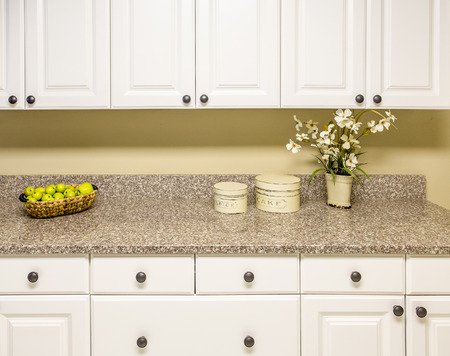 A modern ktichen with white wood cabinets and new granite countertop