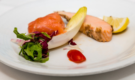 endive: A piece of braised salmon on an appetizer plate with belgian endive