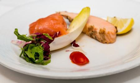 escarola: Un trozo de salm�n cocido en un plato de aperitivo con escarola belga
