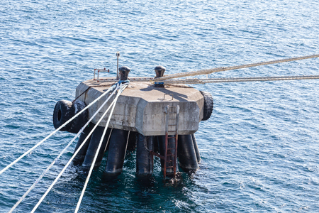 A concrete mooring platform in blue water with many ropes tied to bollards