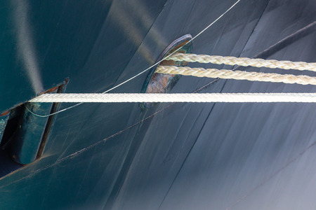 hull: White ropes coming from a blue metal hull on a large ship