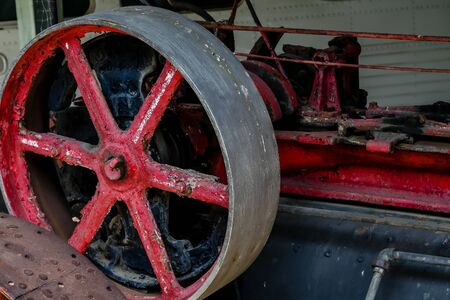 Old rusty machinery with red wheels