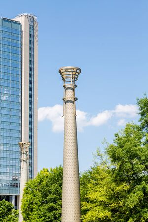 lighting fixtures: Modern lighting fixtures in a park by a blue glass hotel Stock Photo