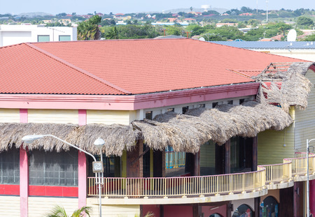 A yellow tropical building with thatched awnings over balcony and a red tile roof Stock Photo