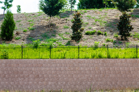 A Block Retaining Wall Topped with Black Iron Fence on a landscaped hill