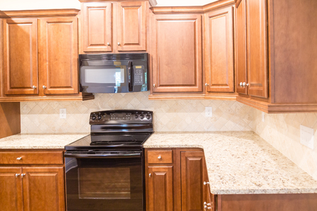 A New Kitchen with Granite Countertops and Black Appliances with wood cabinetry Imagens