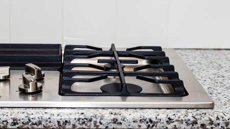cooktop: New stainless steel gas cooktop on a granite countertop Stock Photo