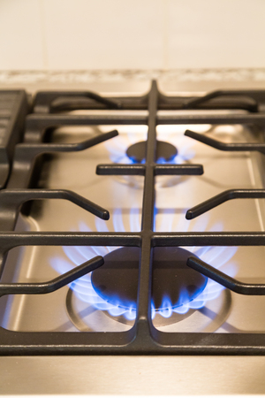 cooktop: Gas flames on modern stainless steel cooktop Stock Photo