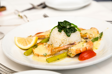 A dinner of broiled shrimp with butter and rice with vegetable garnishes Stock Photo