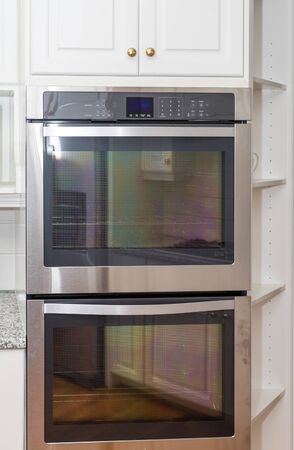 double oven: A new double stainless steel oven in white cabinets Stock Photo