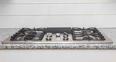 gas stove: New stainless steel gas cooktop on a granite countertop Stock Photo