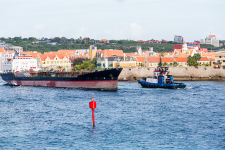 guiding: A tugboat guiding a tanker out of the channel in Curacao