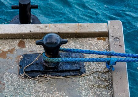 cleat: Ropes to Metal Cleat on Concrete Mooring Platform Stock Photo