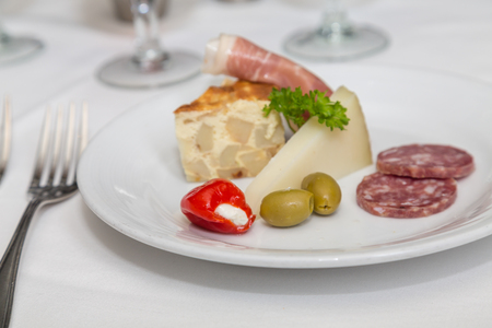 A fresh antipasti plate of quiche, salami, peppers, olives and parmesan cheese