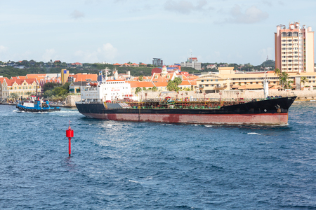 curacao: Tugboats pulling huge tanker from the harbor in Curacao Stock Photo