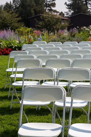 White chairs set up for an outdoor wedding